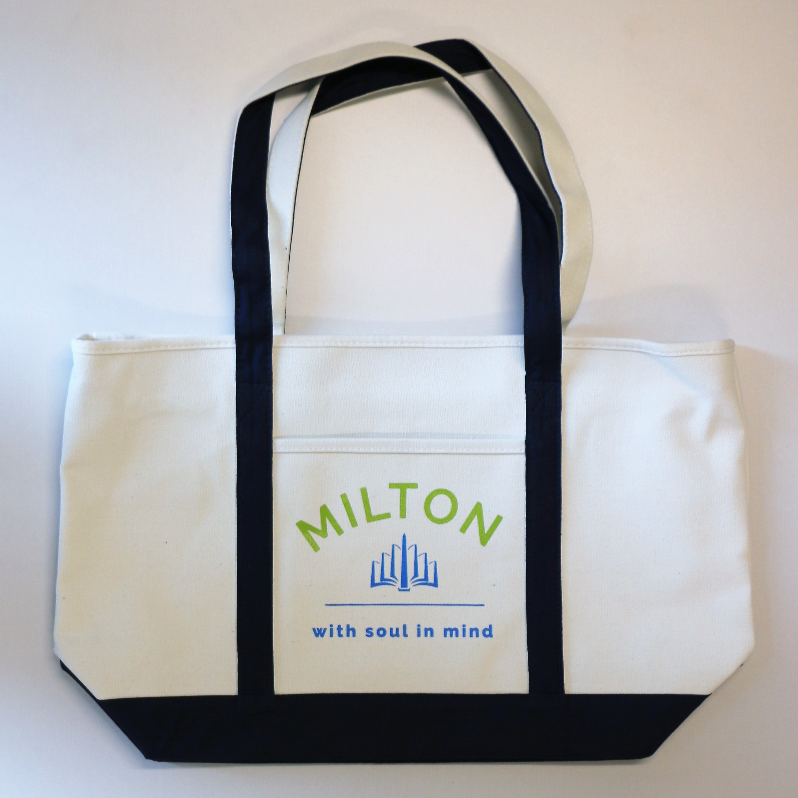 A large canvas tote bag, off-white with a black bottom and straps, and the MILTON logo in color on the side.