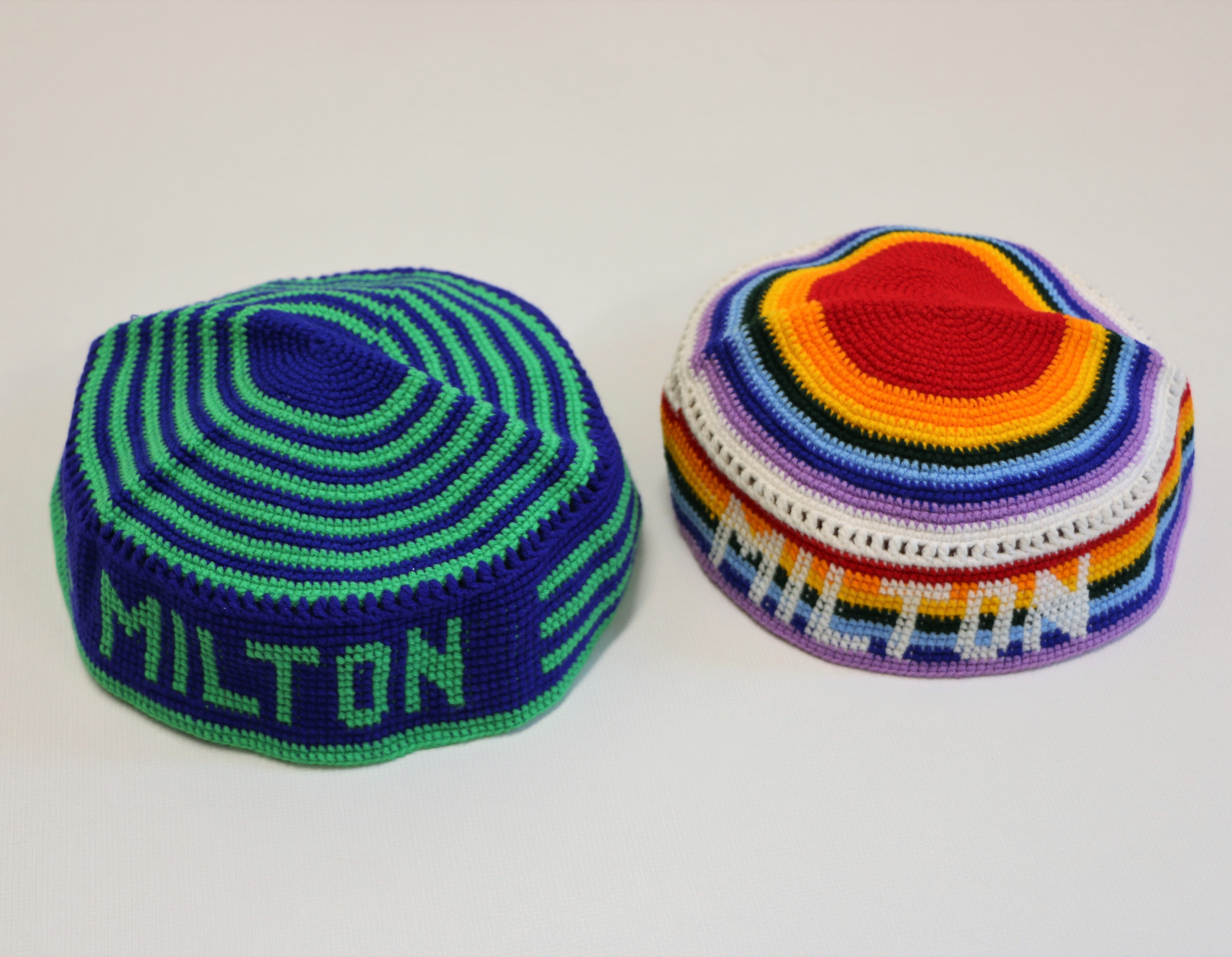 Crocheted kippot that come down the sides of the head. One is blue and green, the other rainbow colored; both have the word